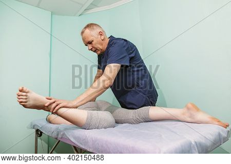 Woman Lying On A Couch And A Chiropractor Works With Her Legs - Physiotherapist Stretching Leg Of Pa