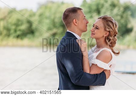 Young Blonde Bride In Rustic Wedding Dress Dances With Her Husband First Dance By Lake Under Branche