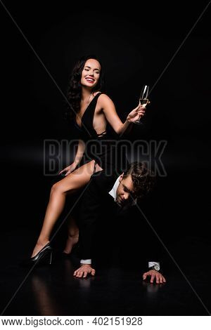 Cheerful Dominant Woman In Dress Sitting Of Submissive Man And Holding Glass Of Champagne On Black