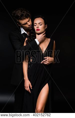 Passionate Man Choking Sexy And Submissive Woman In Dress On Black