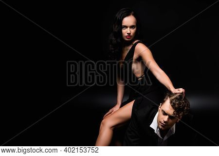 Brunette Dominant Woman In Dress Sitting Of Submissive Man And Pulling Hair On Black
