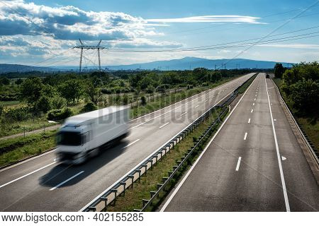 Transportation Truck In High Speed On A Highway Through Rural Landscape. Fast Blurred Motion Drive O