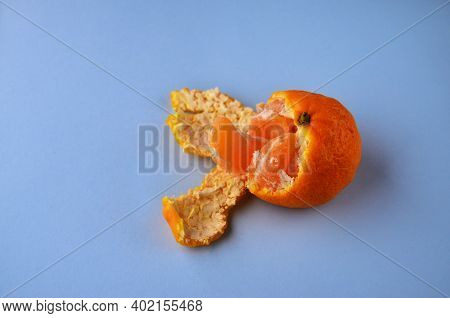 One Half Peeled Tangerine With Peel And A Slice Of Tangerine On A Blue Background With A Copy Space