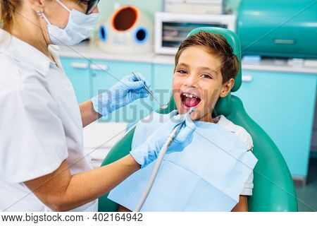 Patient With Open Mouth In Dental Clinic. Preparation For Dental Treatment. Using Cotton Wool To Col