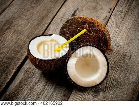 Cocktail Pina Colada. A Fresh Cocktail In Coconut Cup On Wooden Background.