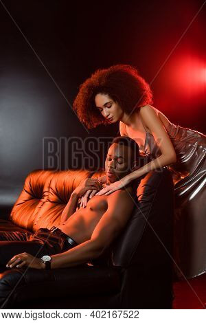 Sexy African American Woman In Dress Seducing Shirtless Man On Sofa And Black Background
