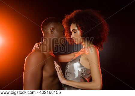 Side View Of Shirtless African American Man Seducing Curly Woman On Black