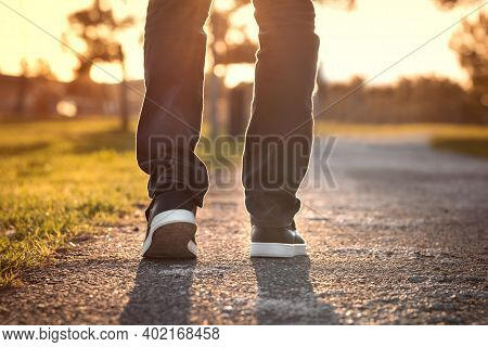 Close Up Of Walking Man At Sunset In The Park. Walking Outdoors. Closeup On Shoe, Taking A Step