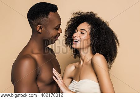 Curly African American Woman Laughing With Happy Boyfriend Isolated On Beige