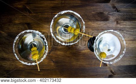 Drink Martini. Three Martini With Olives On A Wooden Table. Top View