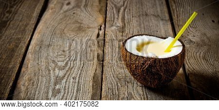 Cocktail Pina Colada. A Fresh Cocktail In Coconut Cup On Wooden Background. Free Space For Text.