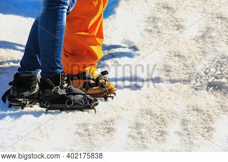 Close Up Of Lower Legs Of Two Travelers Starting Climb To Glacier. Feet Of Couple In Love In Shoes C