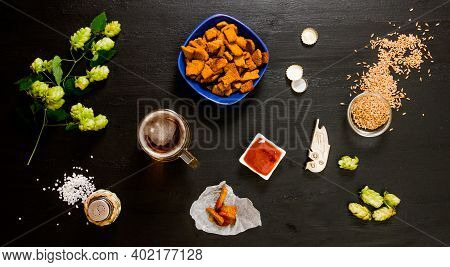Beer Set. A Glass Of Beer, Crackers, Ketchup, Salt. The Ingredients For Brewing: Malt And Hops. On A