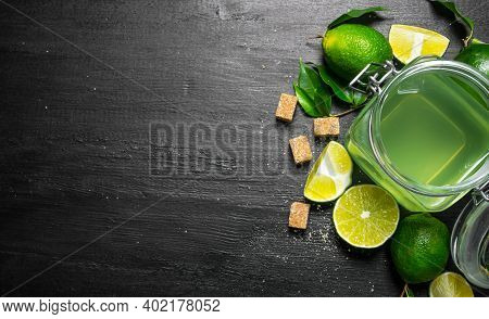 Lime Background. The Juice From The Limes, Sugar And Slices Of Lime. On A Black Wooden Background. F