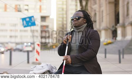 Blind Black Man Sitting On The Bench And Holding Walking Long Cane. High Quality Photo
