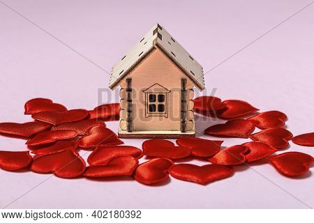 Wooden Toy House And Red Hearts On Pink Background. Sweet Home Or Gift For Valentine's Day Concept.