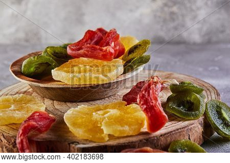 Dried Fruits: Yellow Candied Pineapple Rings, Red Papaya And Green Kiwi On A Wooden Board And In A W