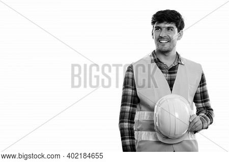 Young Happy Persian Man Construction Worker Smiling And Holding Safety Helmet While Thinking
