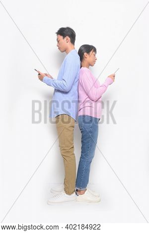 young couple. Man and woman in love in casual clothes, jeans standing back to back, using and texting on their mobile smart phones isolated on white background.