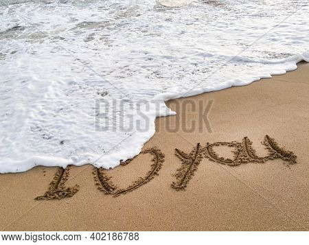 I love you is drawn on the sand. Beautiful view on the waves