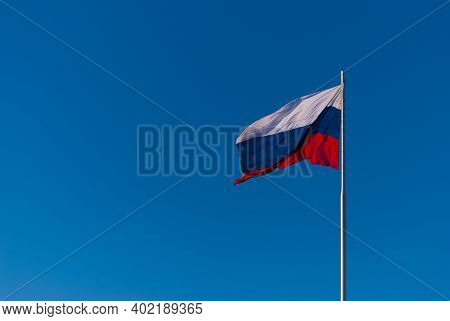 The National Flag Of Russia On The Flagpole Fluttering Wind Against The Blue Sky, Russia