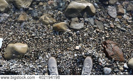 Top View Of Gray Boots Of A Traveler Or Person Having A Rest Standing On A Stone Shore Near The Wate