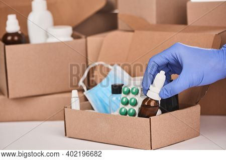 Pharmacists Hand Putting A Bottle Of Nasal Drops Into A Box With Medications