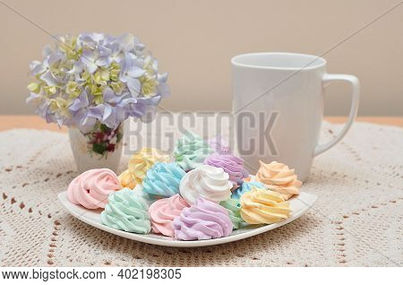 A Tea Setting With A Mug And Plate Of Meringues