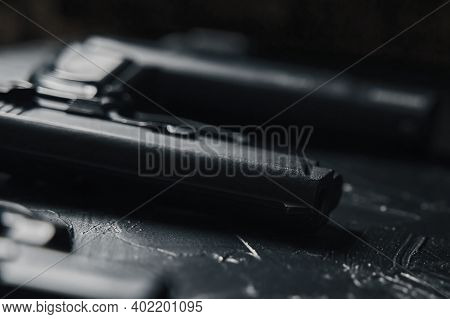 Close-up Of Handguns On Black Table. Dangerous Firearms. Criminal Or Police Arsenal.