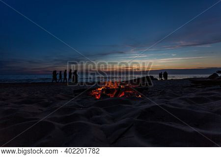 Unrecognisable people celebrating summer solstice with bonfires on beach