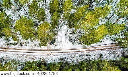 Aerial View Of Black Car On Snow Covered forest road