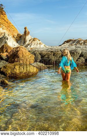 Woman Wading Into Natural Rock Pool In Early Morning Light.  She Is Wearing A Swimming Costume And B