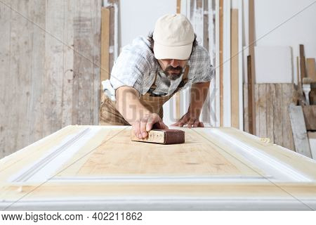 Male Carpenter Working The Wood In Carpentry Workshop, Sanding A Wooden Door With Sandpaper, Wearing
