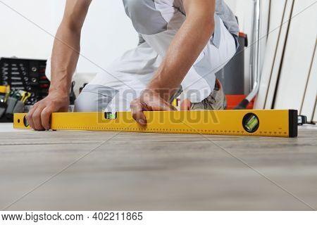 Man Worker Hands Installing Timber Laminate Floor. Precise Finishing Using Spirit Level. Wooden Floo