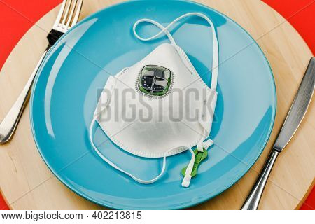 Medical Mask On An Empty Plate With A Fork And Knife On A Wooden Tray. The Concept Of Nutrition And