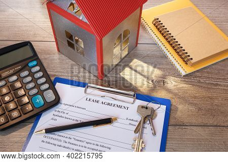 Blank Real Estate Lease Agreement, House Models, Keys And Calculator On Office Desk