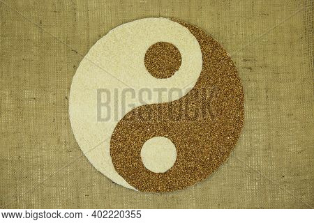 The Concept Of Yin Yang. Sign Yin Yang Against The Background Of Burlap. Rice And Buckwheat Were Use