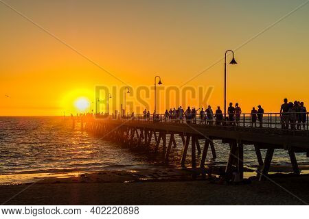 Adelaide, South Australia - March 18, 2017: Crowds Of People Walking Along Glenelg Beach Jetty At Su