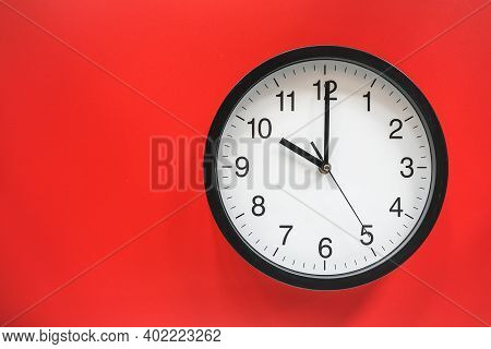 Classic Black And White Analog Clock On Red Background At Ten O\'clock With Copy Space