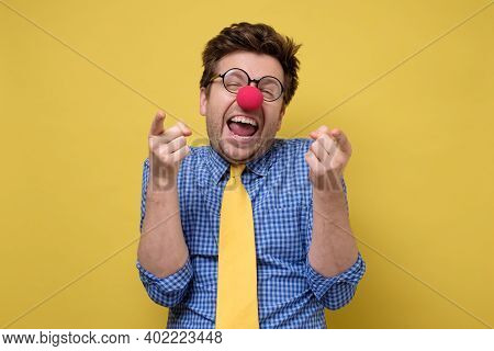 Laughing Young Guy Dressed Lika A Clown Pointing With Finger At Camera.