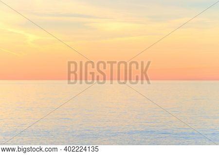 Unfocused Blurred Sunset Over The Sea In Pastel Colors.  Natural Warm Colors Natural Defocused Backg