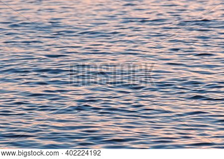 Tranquil Sunset Sea Water Surface. Soft Blurred Water Ripple With Sunny Reflections. Defocused Photo