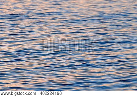 Top View Of Sunset Shine Sea Water Texture.  Pink Ripple Water Surface.  Defocused Photo With Blur I