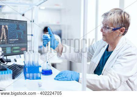 Senior Genetic Researcher Taking Sample From Glass Flask Using Molecular Dispenser. People In Innova