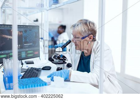 Senior Scientist Doing Medical Analysis And Engineering Using Microscope. Elderly Researcher Carryin