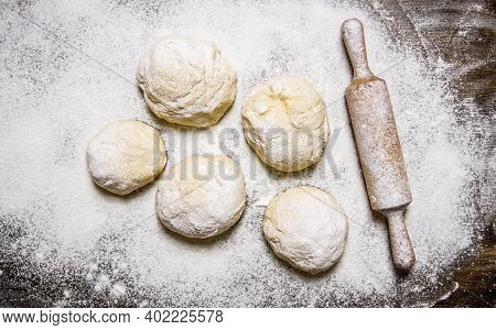 Preparation Of The Dough. The Prepared Dough With Flour And With A Rolling Pin. On A Wooden Table. T