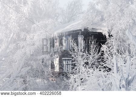 Old Wooden House Surrounded By Snow-covered Trees On A Winter Day