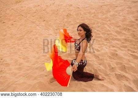 Dancer In The Desert With Flowing Silk Fabrics.
