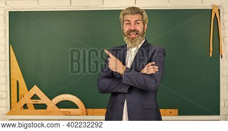 Teacher Explain Hard Topic. Man Teacher In Front Of Chalkboard. Important Information To Remember. T