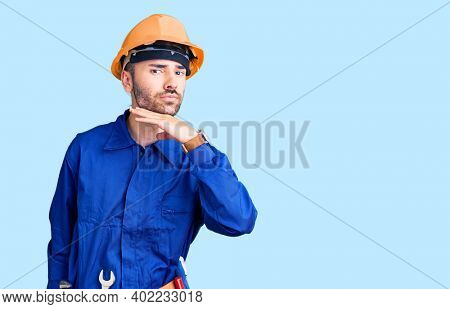 Young hispanic man wearing worker uniform cutting throat with hand as knife, threaten aggression with furious violence